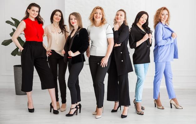Un gruppo di donne vestite in stile business stanno insieme e posano davanti alla telecamera.