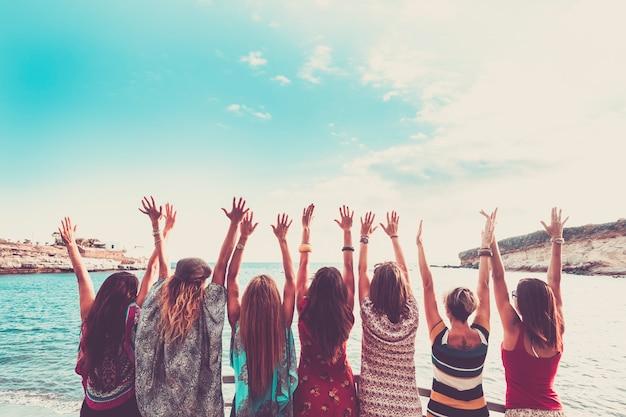 Gruppo di donne che si godono e festeggiano le vacanze estive tutte insieme salutando l'oceano e la natura giovani attività per il tempo libero tutte le mani in alto e abiti di moda stile vintage colori