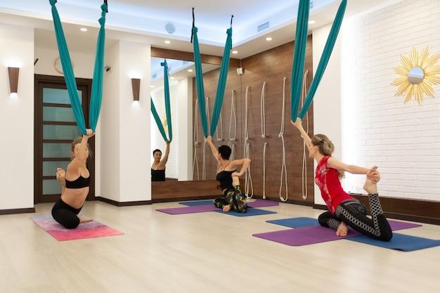 Le donne del gruppo volano yoga allungando esercizi in palestra