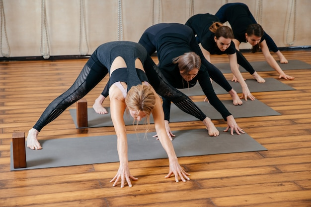 Gruppo di donne che praticano yoga stretching utilizzando blocchi di legno, esercizi per la flessibilità della colonna vertebrale e delle spalle