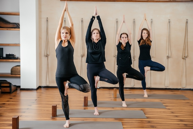 Gruppo di donne che praticano yoga stretching utilizzando blocchi di legno, esercizi per colonna vertebrale e spalle