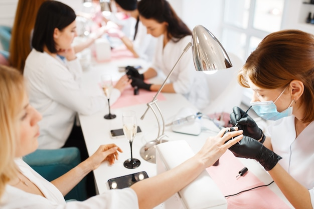 Il gruppo di donne si distende sulla procedura di manicure nel salone di bellezza.