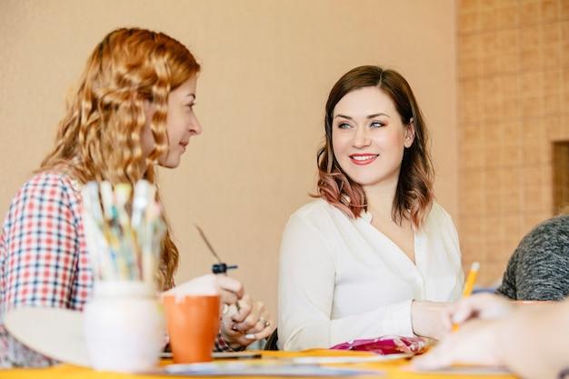 Un gruppo di donne sorridenti parlano felice all'addestramento artistico sulla creazione della vita del mandala