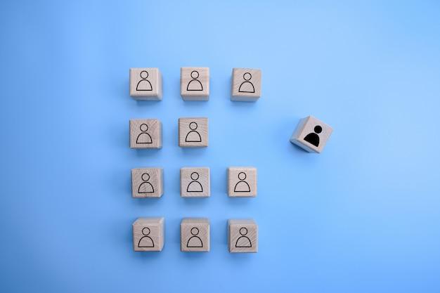 Gruppo di cubi di legno con l'icona di persona su di loro con uno in piedi fuori dalla folla