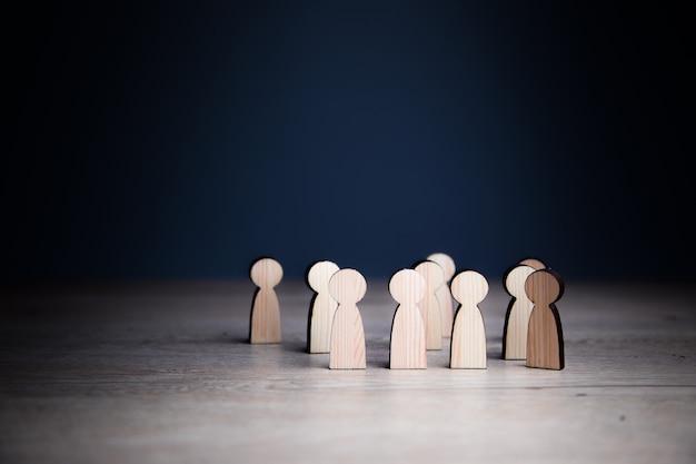 Gruppo di persone di giocattoli in legno su una superficie di legno