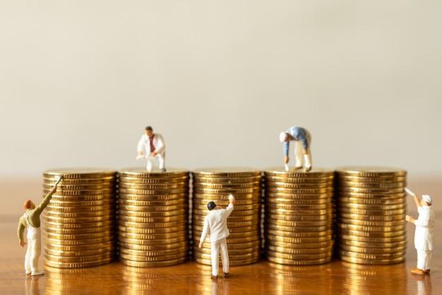 Gruppo di figure in miniatura di lavoratori persone che puliscono e dipingono una pila di monete d'oro su un tavolo di legno