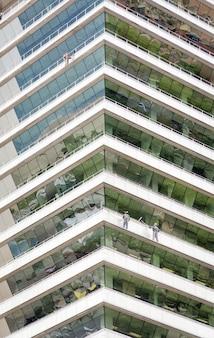 Gruppo di lavoratori che puliscono le finestre di un grattacielo