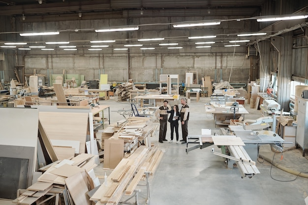 Gruppo di operai della fabbrica contemporanea che discute mobili che producono materiali mentre il responsabile delle vendite li indica alla riunione