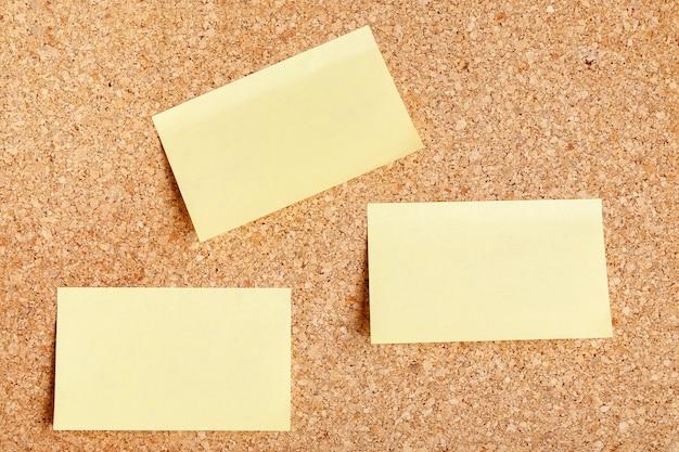 Gruppo di mockup adesivo in bianco giallo con appuntato sulla bacheca di sughero