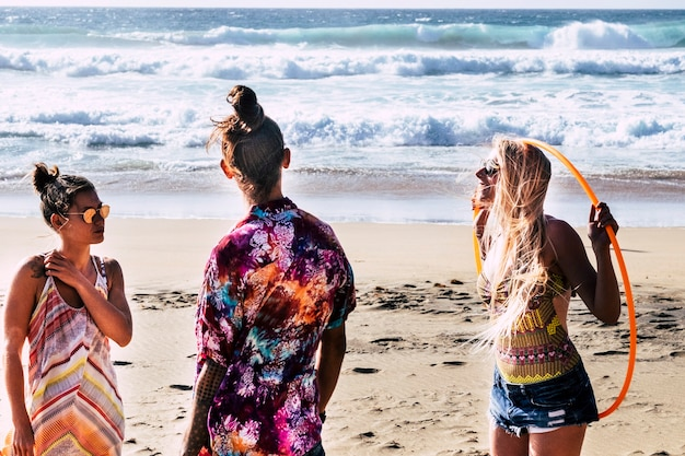 Un gruppo di giovani amici adulti in spiaggia con abiti colorati si diverte in amicizia e si gode l'estate insieme