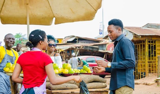 Gruppo di giovani africani che fanno transazione in un luogo di mercato