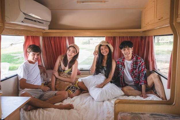 Gruppo di giovani amici asiatici divertendosi all'interno del camper nel fine settimana