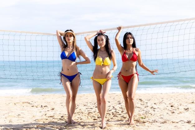 Gruppo di giovani ragazze asiatiche in bikini che giocano a pallavolo sulla spiaggia, gruppo di amiche che giocano a beach volley, gruppo di amici felici gioca con la palla sulla spiaggia al tramonto.