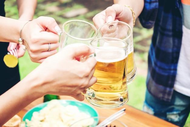 Gruppo di giovani asiatici che celebrano i festival della birra felici mentre godono della festa domestica