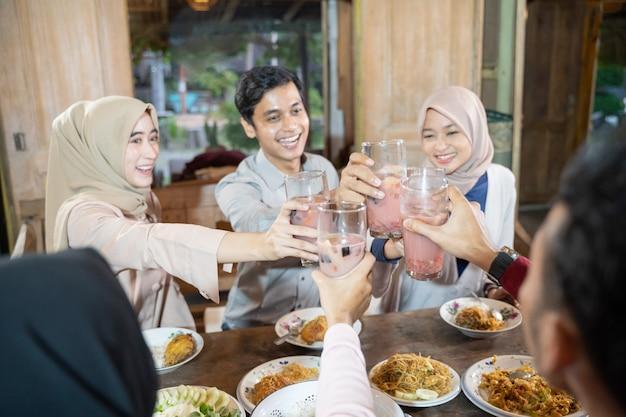 Gruppo di giovani asiatici che celebrano e alzano bicchieri di ghiaccio alla frutta per brindare mentre si rompono velocemente