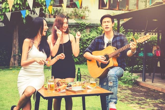 Il gruppo di giovani asiatici felici mentre gode del ricevimento in giardino e gioca la chitarra sulla casa del giardino
