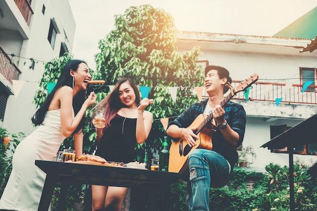 Il gruppo di giovani asiatici felici mentre gode del partito domestico e gioca la chitarra sulla casa del giardino