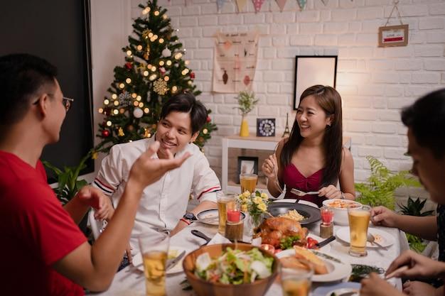 Gruppo di giovani asiatici che hanno una festa a casa. mangiano e bevono birra mentre parlano.