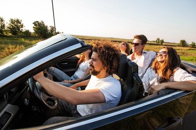 Un gruppo di giovani belle ragazze e ragazzi in occhiali da sole sorridono e cavalcano in una cabriolet nera sulla strada in una giornata di sole. .