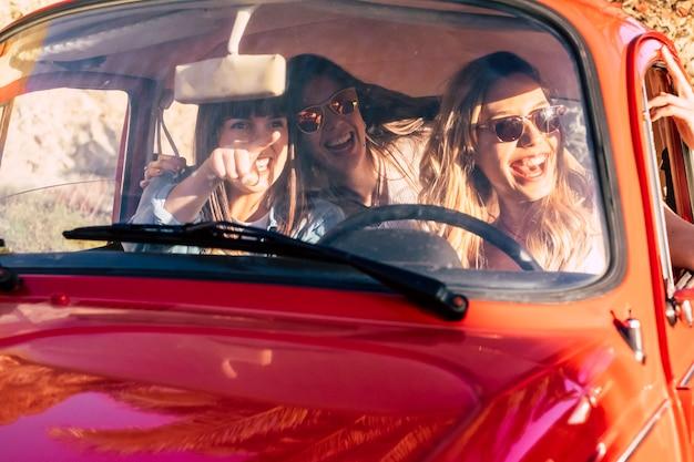 Un gruppo di giovani belle amiche all'interno di una vecchia auto d'epoca rossa si gode il viaggio e guida in una bella giornata di sole