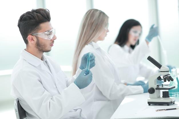 Gruppo di giovani biologi seduti al tavolo del laboratorio. scienza e salute