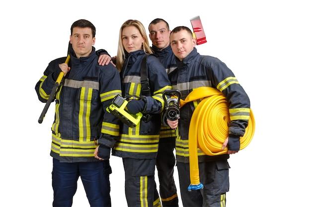 Gruppo di giovani vigili del fuoco coraggiosi in uniforme isolato