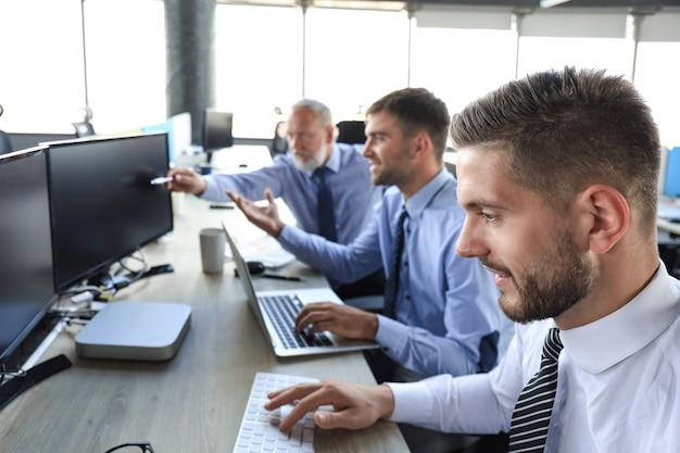 Gruppo di giovani uomini d'affari in abiti da cerimonia che lavorano utilizzando i computer seduti in ufficio.