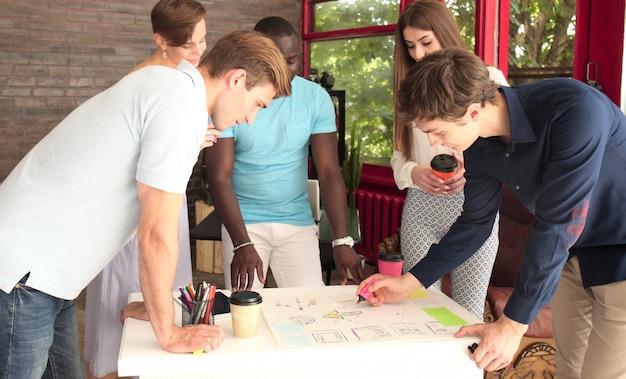 Gruppo di giovani imprenditori e designer. lavorano su un nuovo progetto. concetto di avvio.
