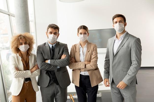 Un gruppo di giovani imprenditori in piedi in ufficio e indossano maschere come protezione dal virus corona