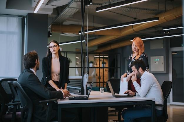 Gruppo di giovani imprenditori che lavorano e comunicano insieme in ufficio creativo