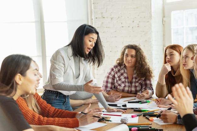 Gruppo di giovani impiegati caucasici che si incontrano per discutere nuove idee