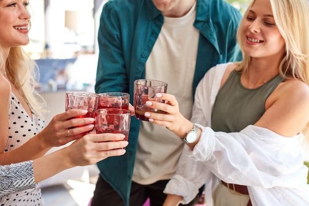 Un gruppo di giovani caucasici festeggia il compleanno con un bicchiere di bevanda tintinnante