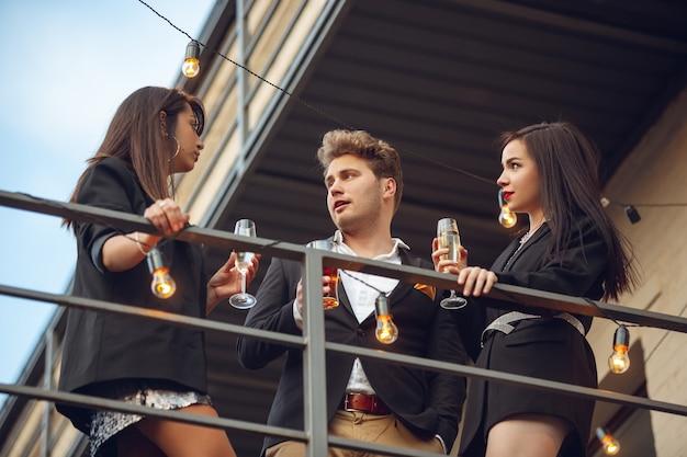 Gruppo di giovani caucasici che celebrano, sembrano felici, organizzano una festa aziendale in ufficio o al bar