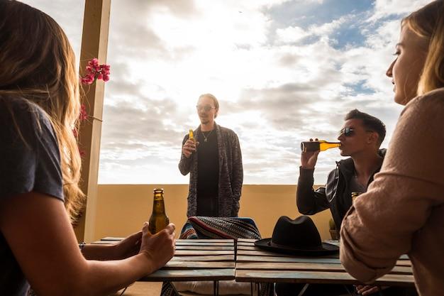 Un gruppo di giovani caucasici sta insieme nella terrazza sul tetto parlando e bevendo birra