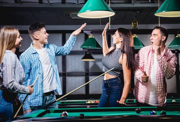 Gruppo di giovani amici allegri che giocano a biliardo.