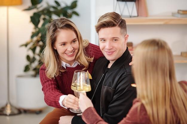 Gruppo di giovani amici interculturali allegri in abbigliamento casual intelligente riuniti attorno a un piccolo tavolo rotondo bianco in soggiorno e giocando a giochi di nome
