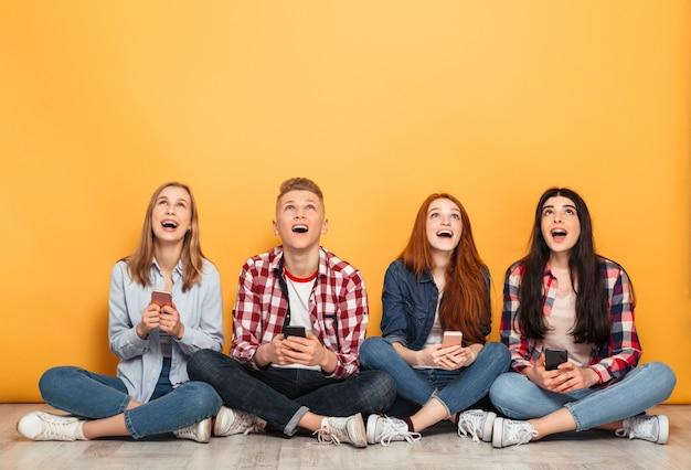 Gruppo di giovani compagni di scuola allegri che utilizzano i telefoni cellulari