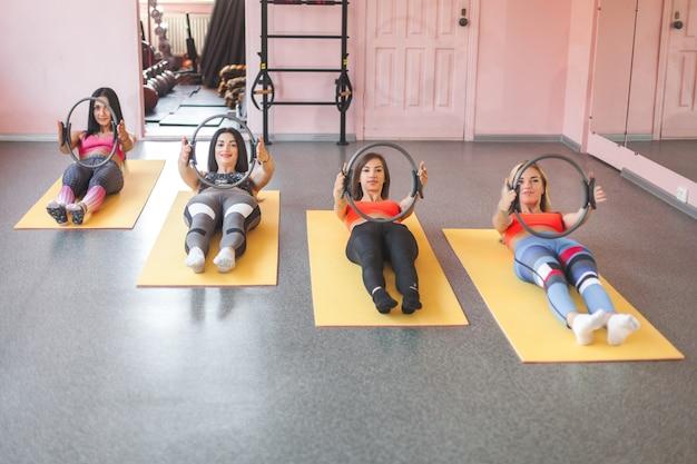 Il gruppo di giovani donne allegre che fanno i pilates si esercita con gli anelli di forma fisica