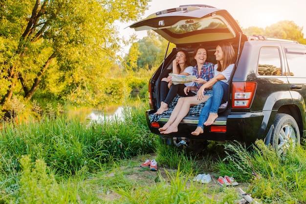 Un gruppo di giovani donne allegre viaggia nella natura in auto