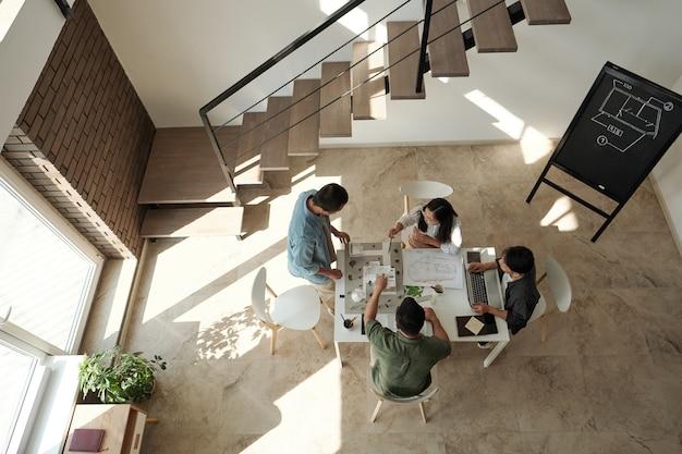 Gruppo di giovani architetti cinesi riuniti al tavolo per la discussione del nuovo progetto