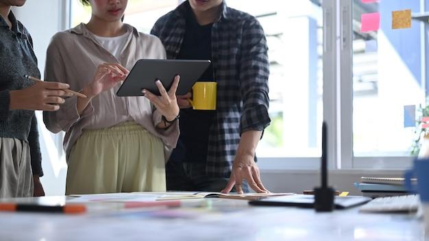 Gruppo di giovani designer che discutono idee per una nuova strategia di sviluppo in ufficio creativo