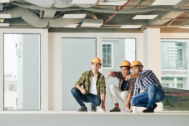 Gruppo di giovani ingegneri che discutono il piano delle linee di servizio prima di iniziare i lavori all'interno del nuovo edificio