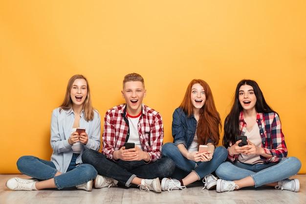 Gruppo di giovani compagni di scuola entusiasti che utilizzano i telefoni cellulari