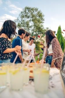 Gruppo di giovani amici che cucinano salsicce e si divertono in un barbecue estivo all'aperto