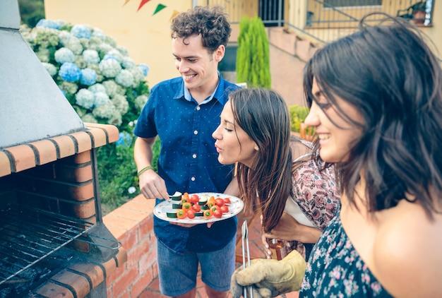 Gruppo di giovani amici che cucinano spiedini di verdure e si divertono in un barbecue estivo all'aperto