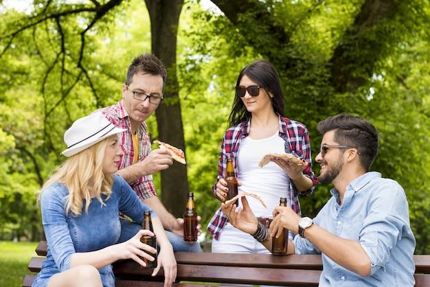 Gruppo di giovani amici che bevono birra e mangiano pizza su una panchina del parco insieme