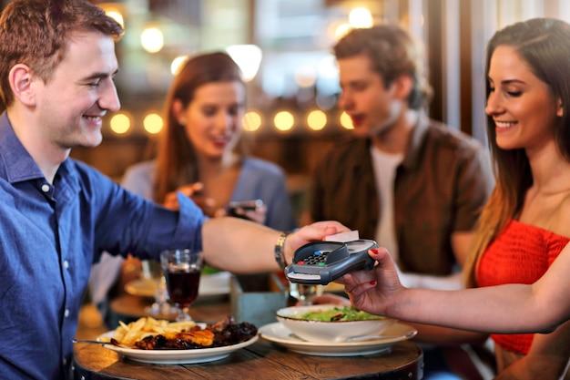 Gruppo di giovani amici che godono del pasto nel ristorante
