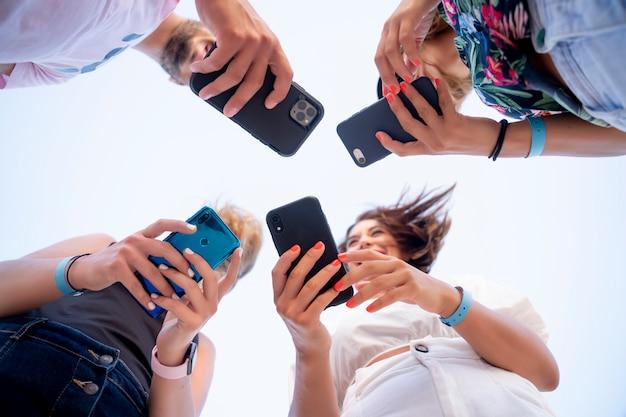 Gruppo di giovani amici che utilizzano il telefono cellulare mobile.