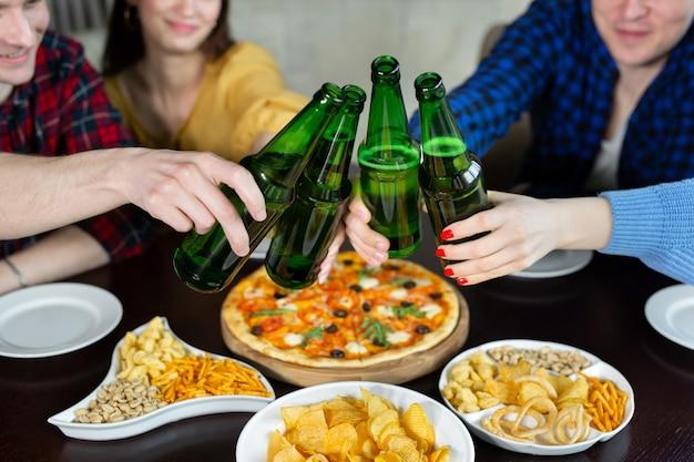 Gruppo di giovani amici con pizza e bottiglie di bevanda che celebra