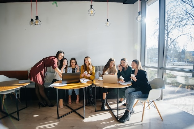 Un gruppo di ragazze si siede in un ufficio davanti ai computer e discute dei progetti. comunicazione e formazione online.